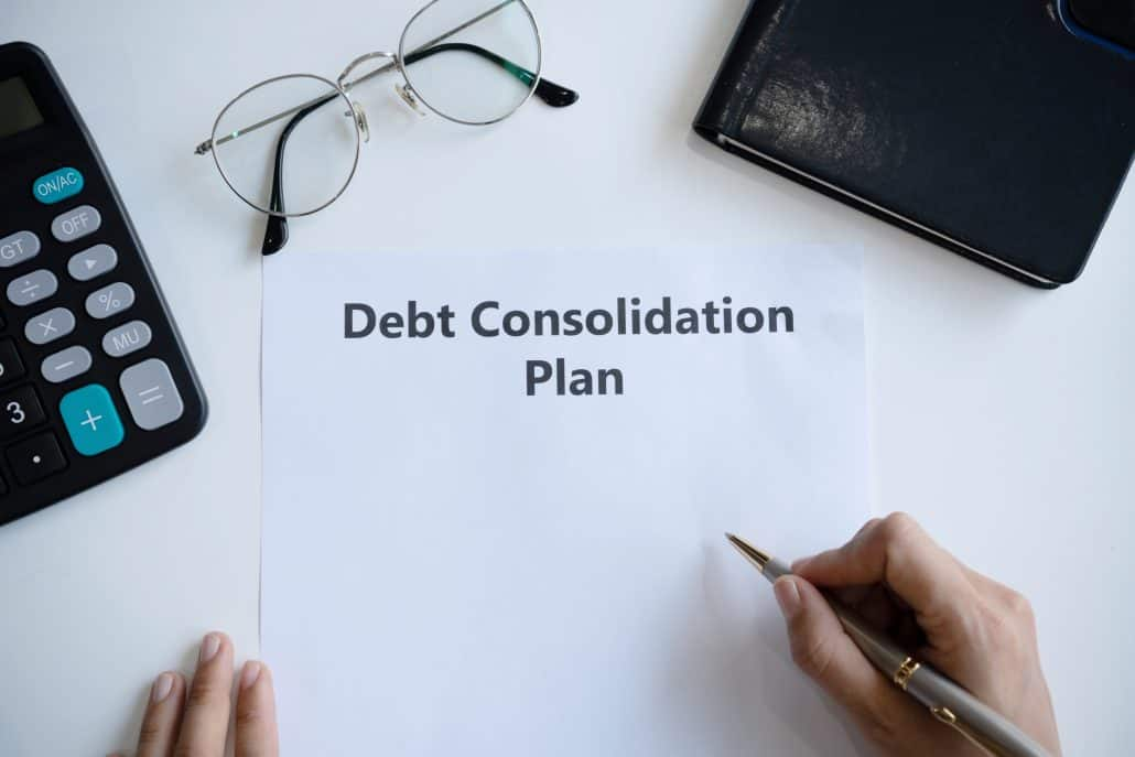 A person writing debt consolidation plan in paper