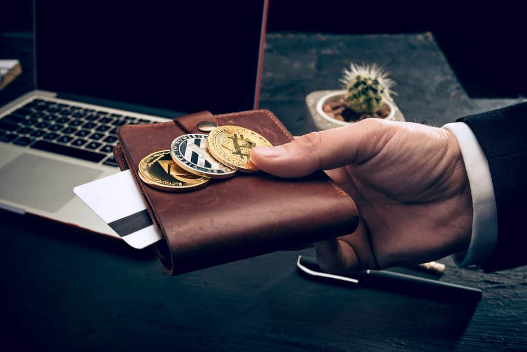 A man holds  golden bitcoin and wallet in hands